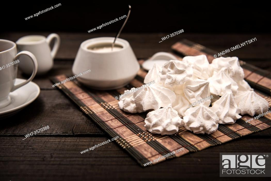 Imagen: bizet on a brown wooden table with a cup of tea, sugar and milk.