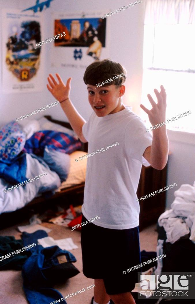 Stock Photo: young boy standing in a messy room.