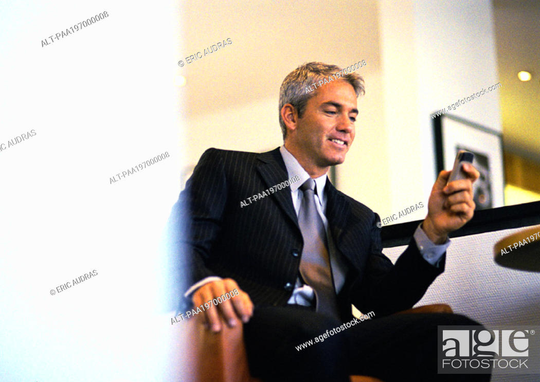 Stock Photo: Businessman sitting holding cell phone.