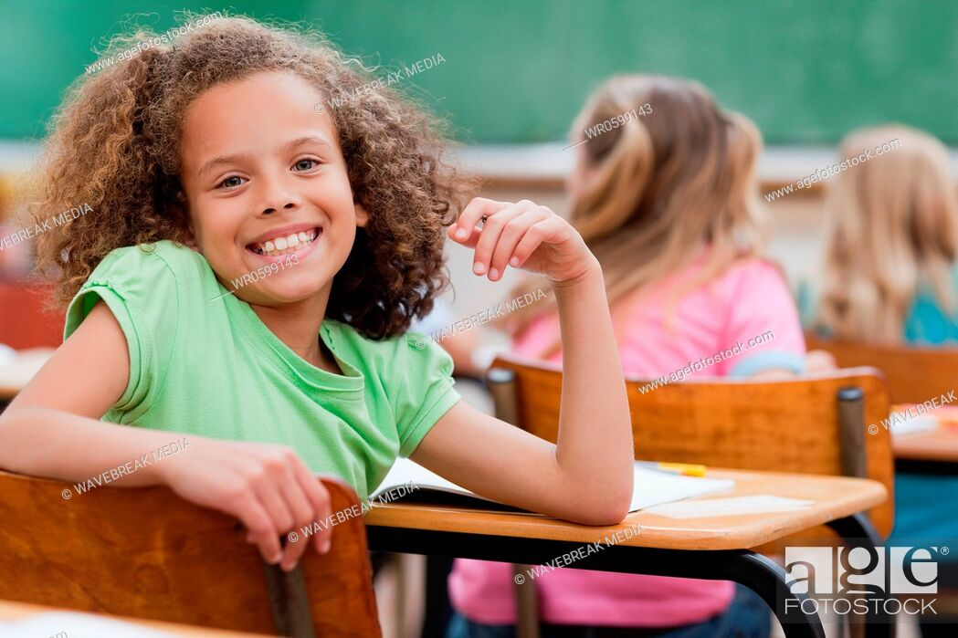 Stock Photo: Happy girl turned around during class.