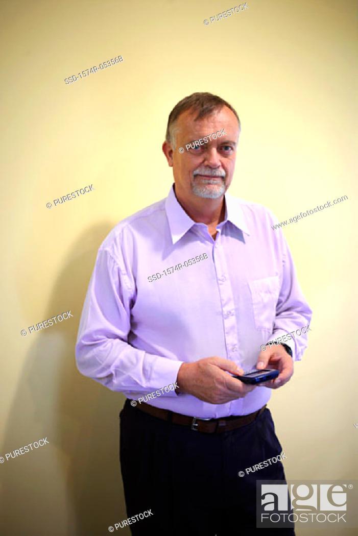 Stock Photo: Portrait of a businessman holding a palmtop.