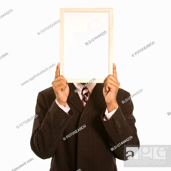 Stock Photo: Man holding blank sign over his face standing against white background.
