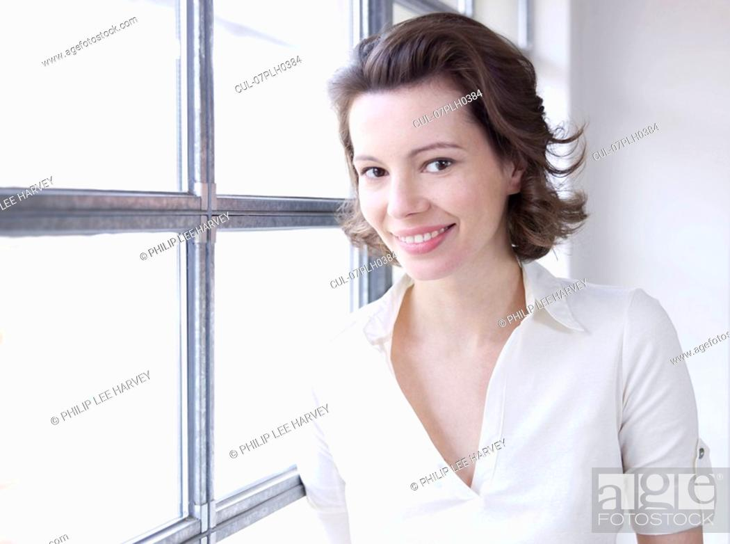 Stock Photo: Woman against window, smiling to camera.