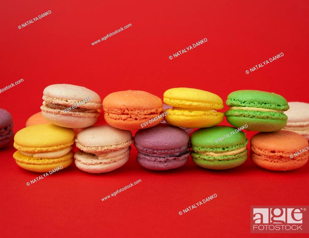 Stock Photo: pile of multi-colored baked macarons almond flour cakes on a red background, close up.