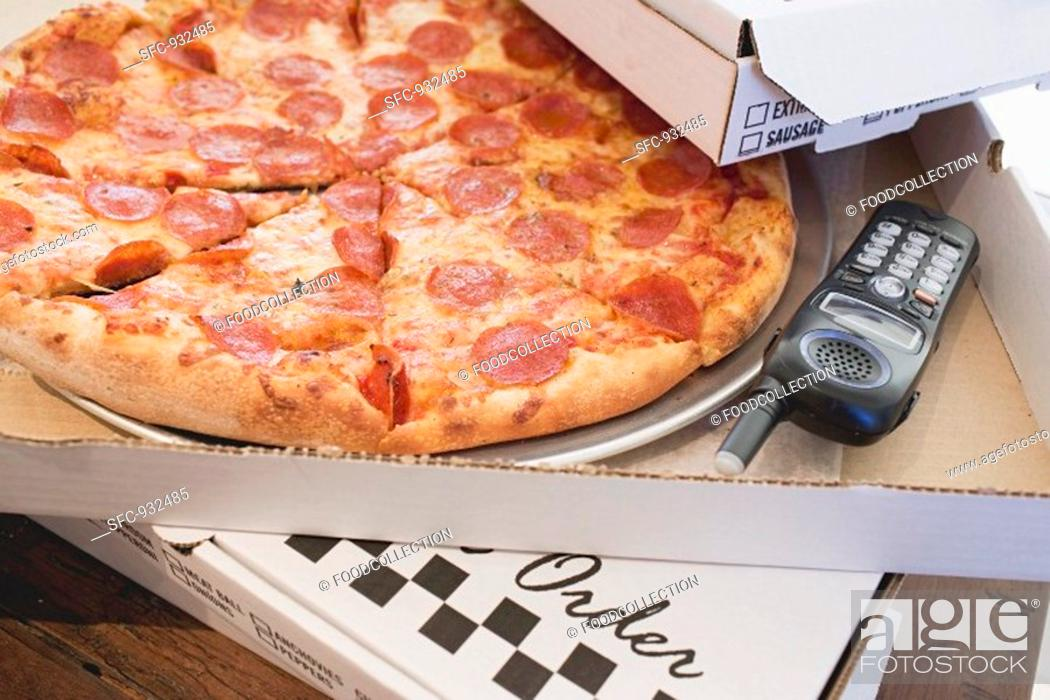 Stock Photo: Pepperoni pizza in pizza box, telephone beside it.