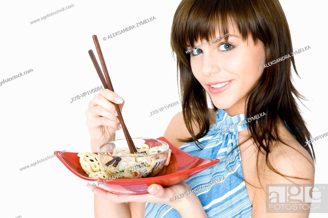 Stock Photo: young woman eating asian noodles.