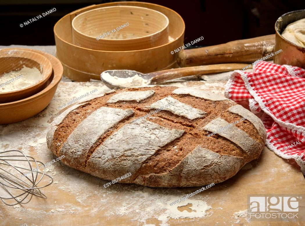 Stock Photo: baked loaf of bread on the table and ingredients, kitchen utensils lie nearby, top view.