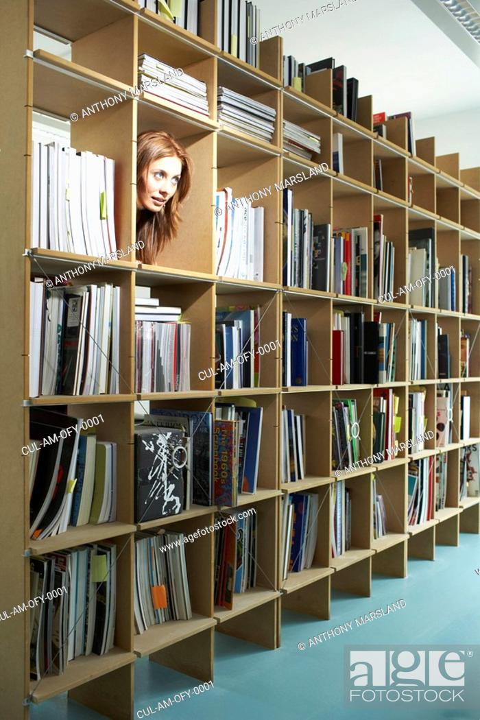 Stock Photo: Woman peeping head through bookshelf.
