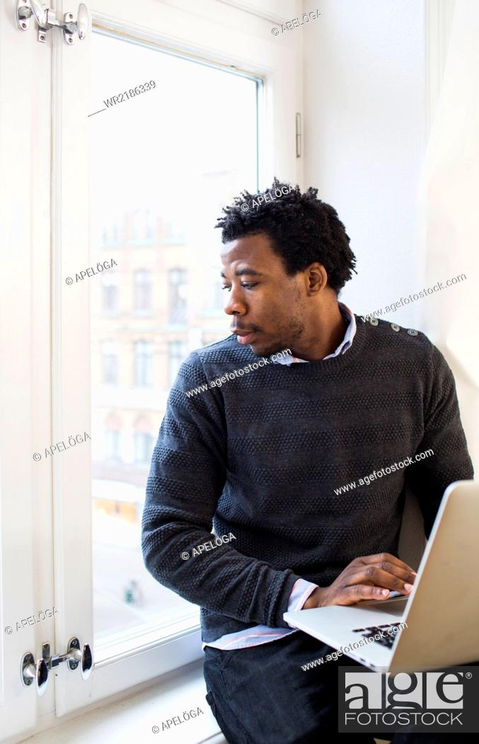Stock Photo: Young businessman using laptop while looking through window.