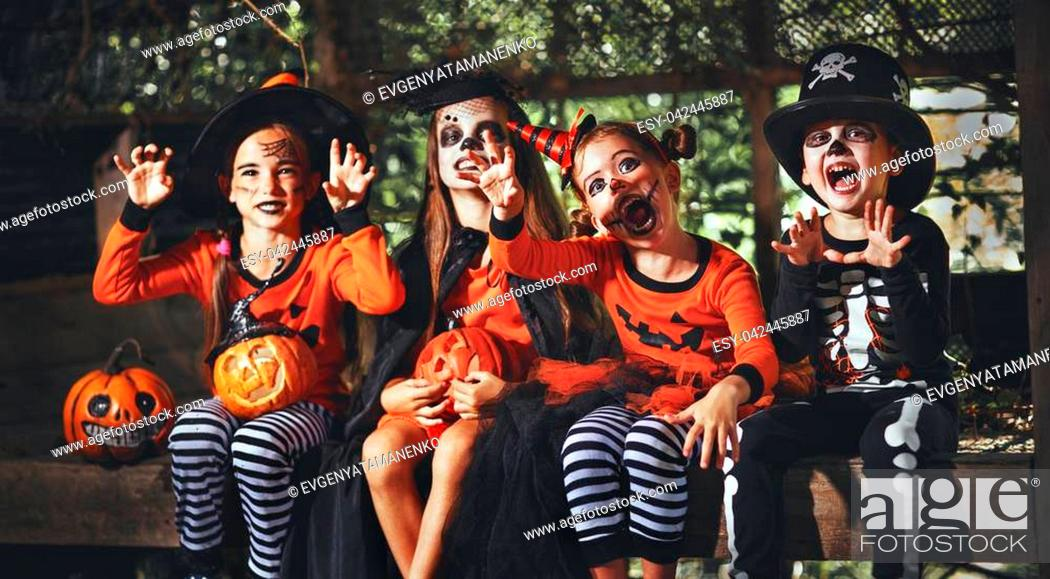 Photo de stock: happy Halloween! a group of children in suits and with pumpkins in the forest.