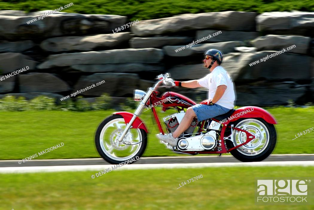 Stock Photo: Male wearing protective helmet riding a red motorcycle for pleasure.