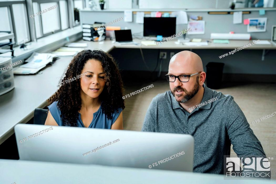 Stock Photo: Coworkers using computer in office.