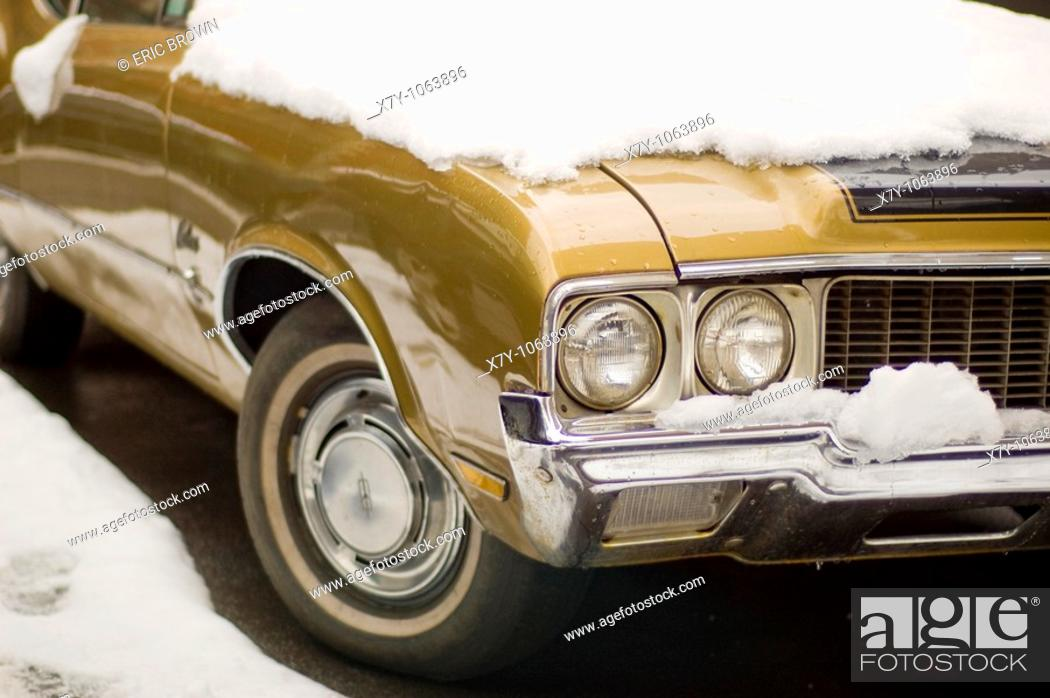 Stock Photo: A classic Oldsmobile is partially covered in snow.