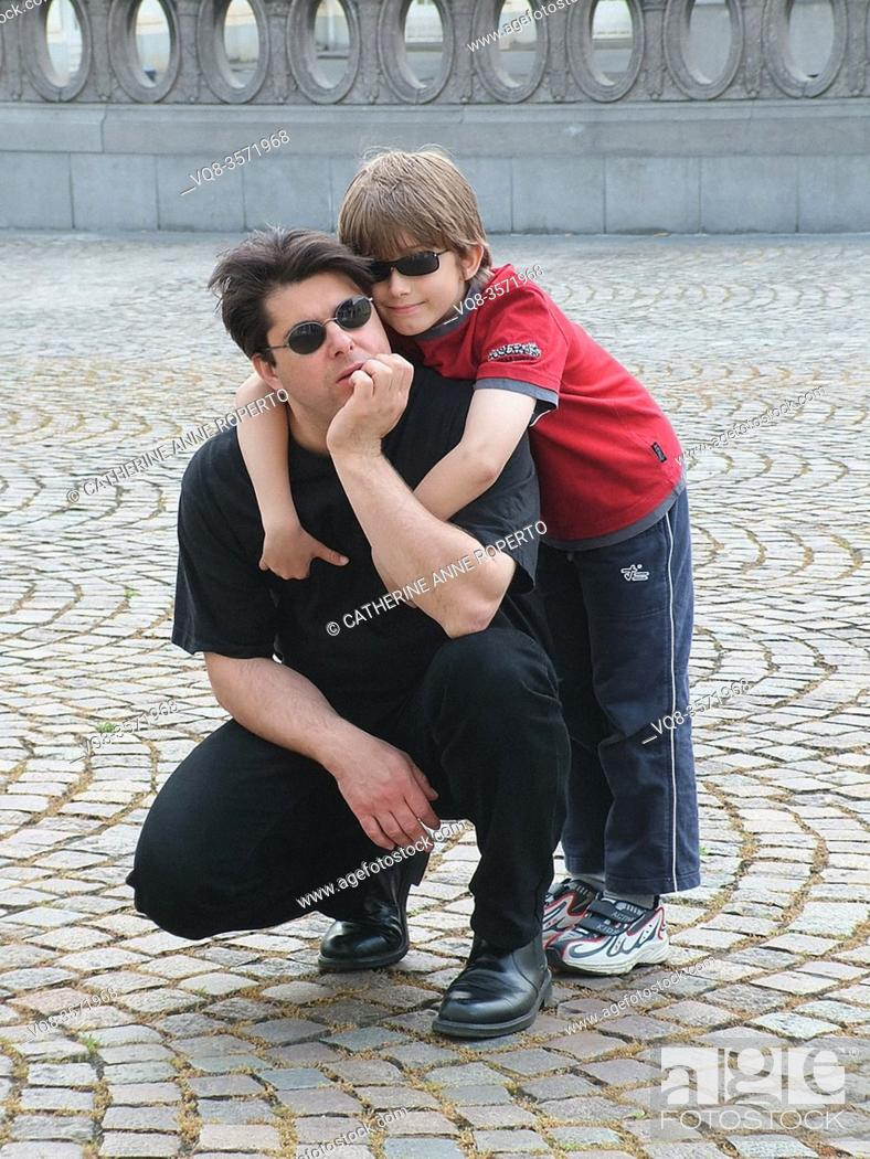 Stock Photo: Boy and kneeling man both wearing black sunglasses hug on the fan shaped cobbles in front of an elipical stone balustrade in Belgium.