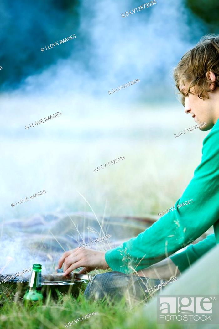 Stock Photo: A young man having a barbecue.