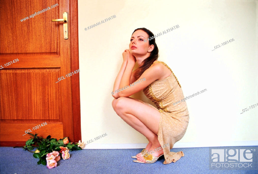 Stock Photo: Woman cowering in front of a bunch of roses.