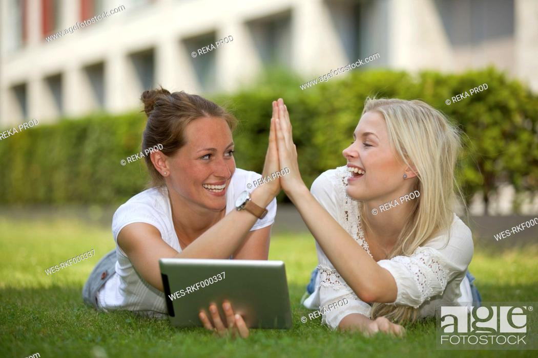 Stock Photo: Germany, North Rhine Westphalia, Cologne, Young students with digital tablet, smiling.