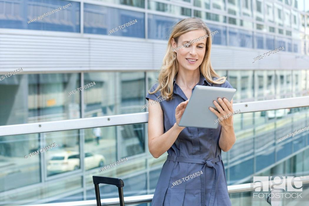 Stock Photo: Smiling blond businesswoman using tablet.