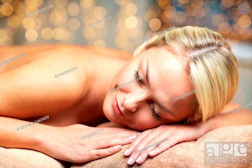 Stock Photo: people, beauty, spa, healthy lifestyle and relaxation concept - close up of beautiful young woman lying on massage table in spa.