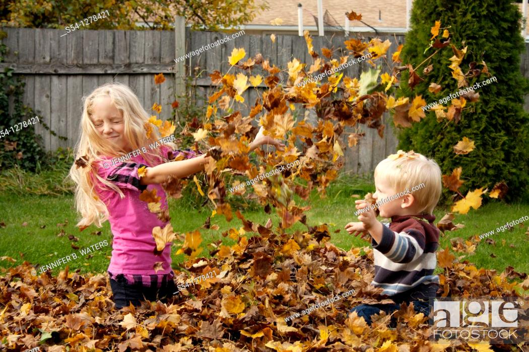 Stock Photo: A girl, 5-10 and and a toddler play in a pile of leaves in the fall.