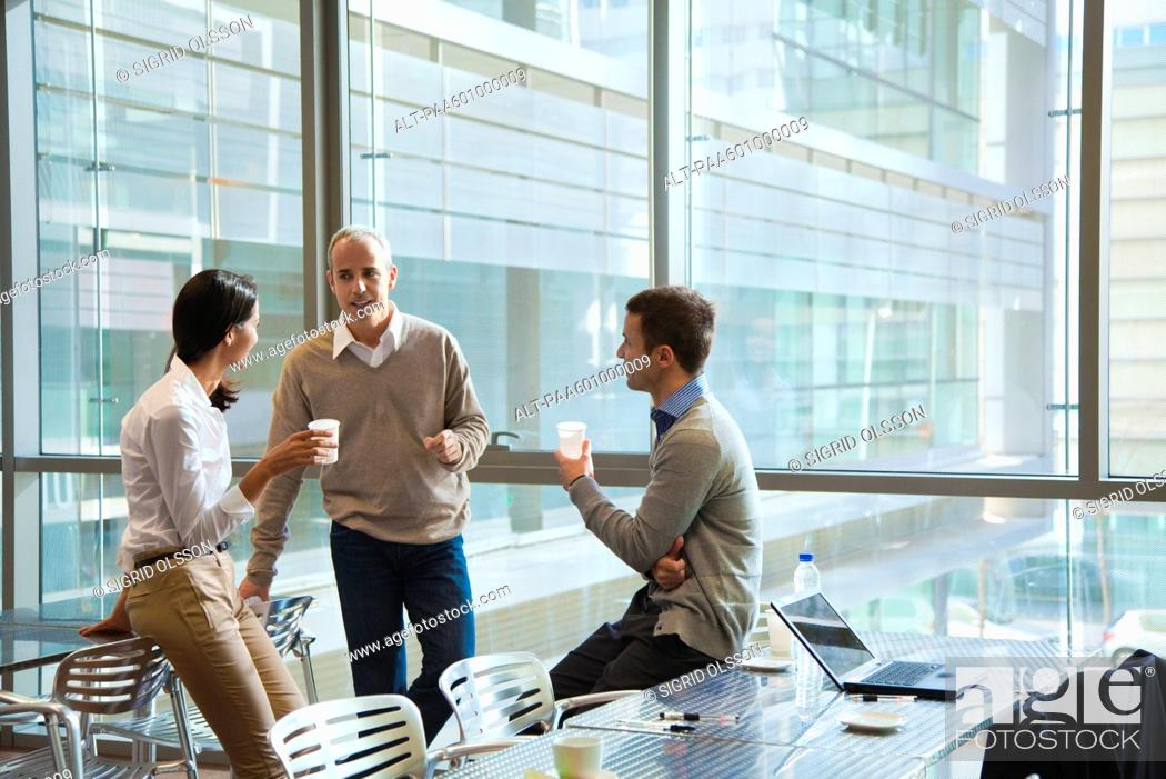 Stock Photo: Colleagues taking coffee break in office cafeteria.