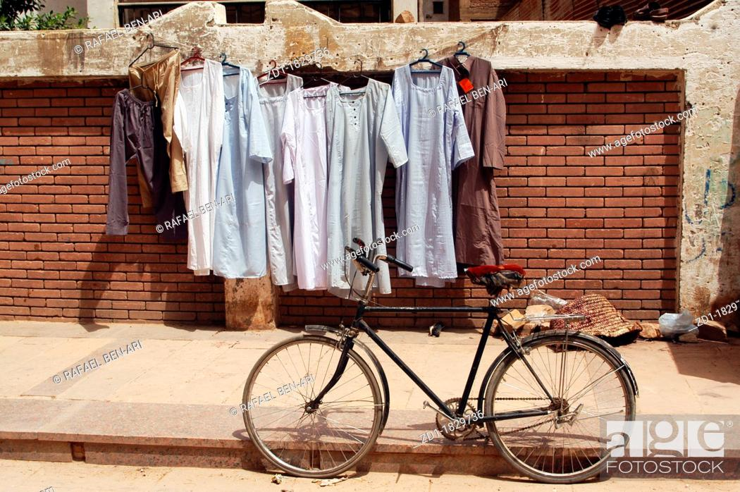 Stock Photo: Galabayyas hanging on a clothes line on a street with a bike in Cairo, Egypt.