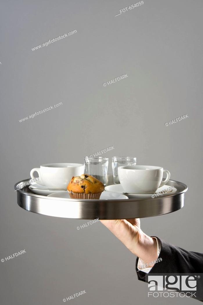 Stock Photo: A waiter holding a tray with coffee cupy and muffin.