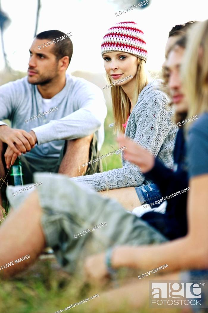Stock Photo: A group of young friends sitting outdoors.