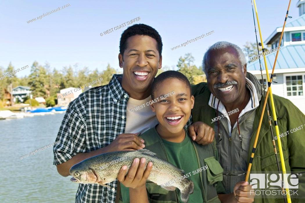 Stock Photo: Male members of three generation family showing fish smiling portrait.