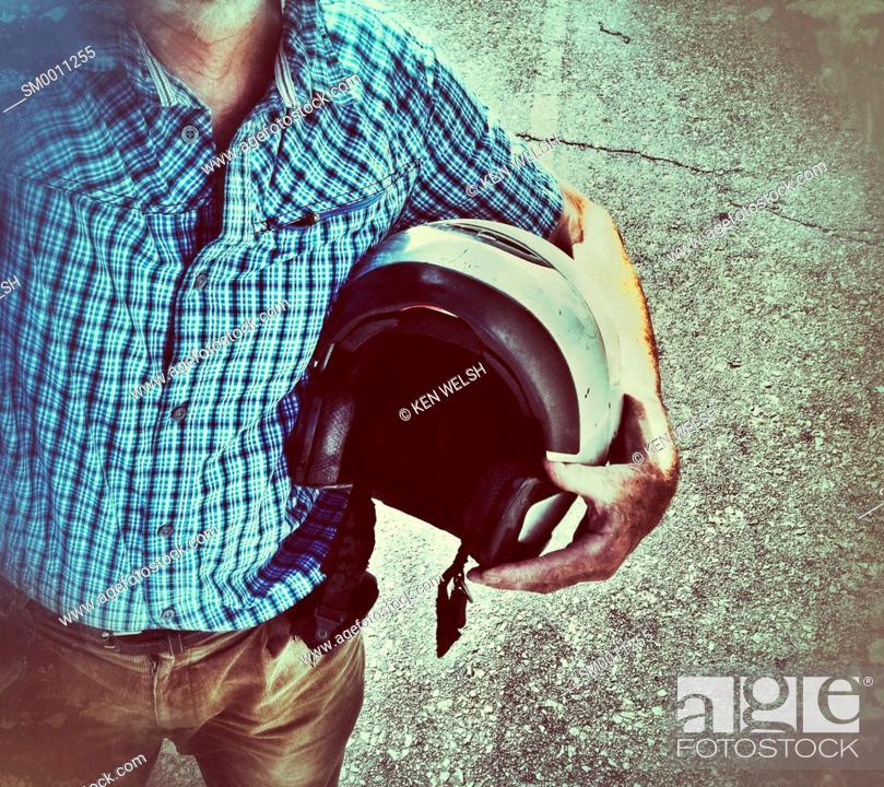 Imagen: Man carrying motorcycle helmet under arm.