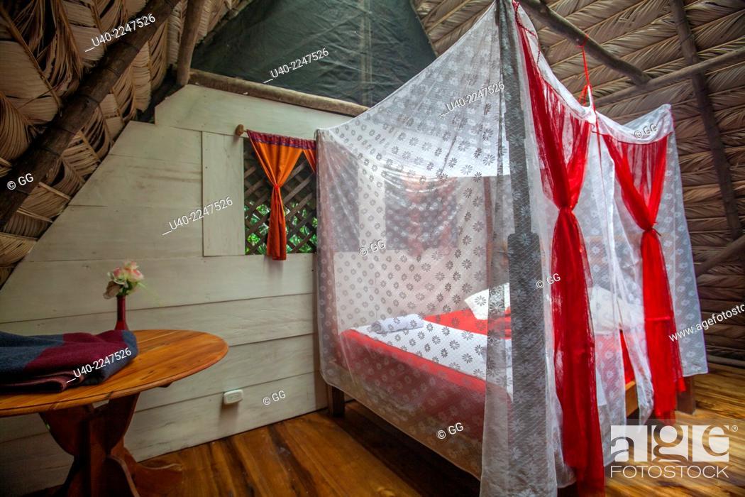 Stock Photo: Guatemala, Rio Dulce, Finca Tatin, bedromm with mosquito net bed.