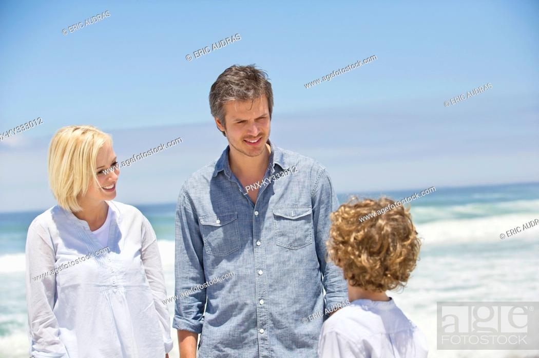 Stock Photo: Couple talking to their son on the beach.