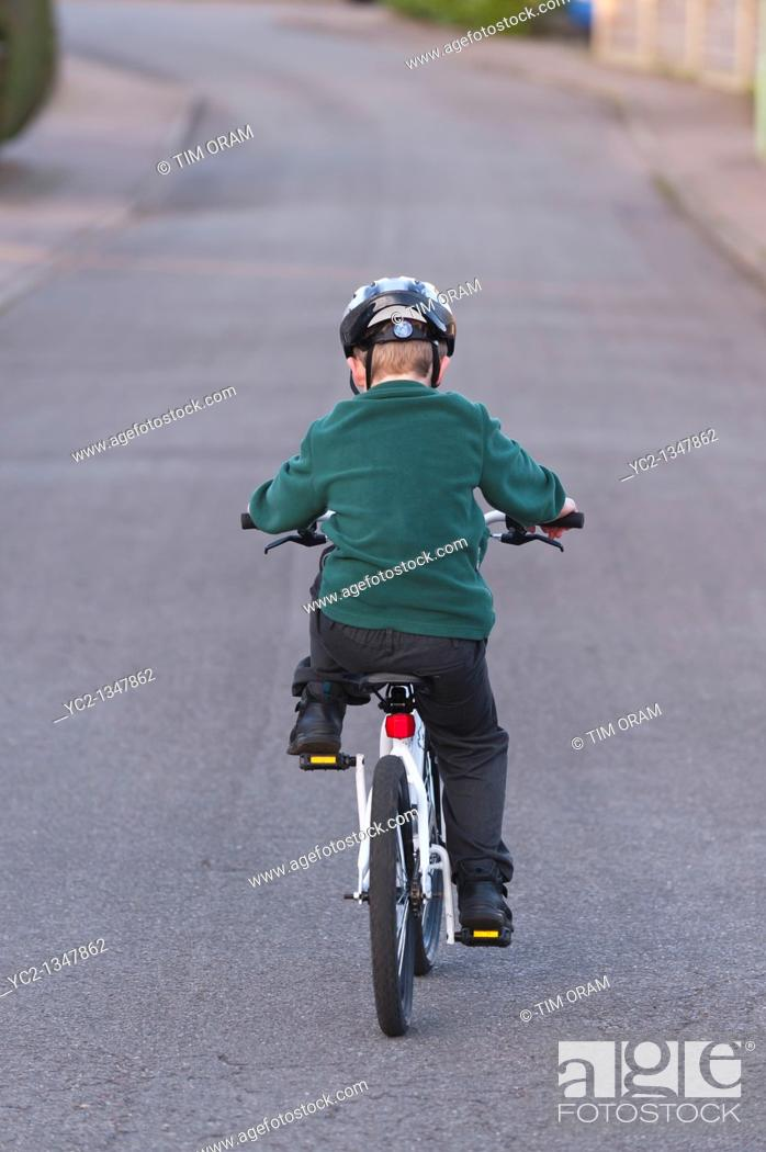 Stock Photo: A seven year old boy riding his BMX bike in the Uk.
