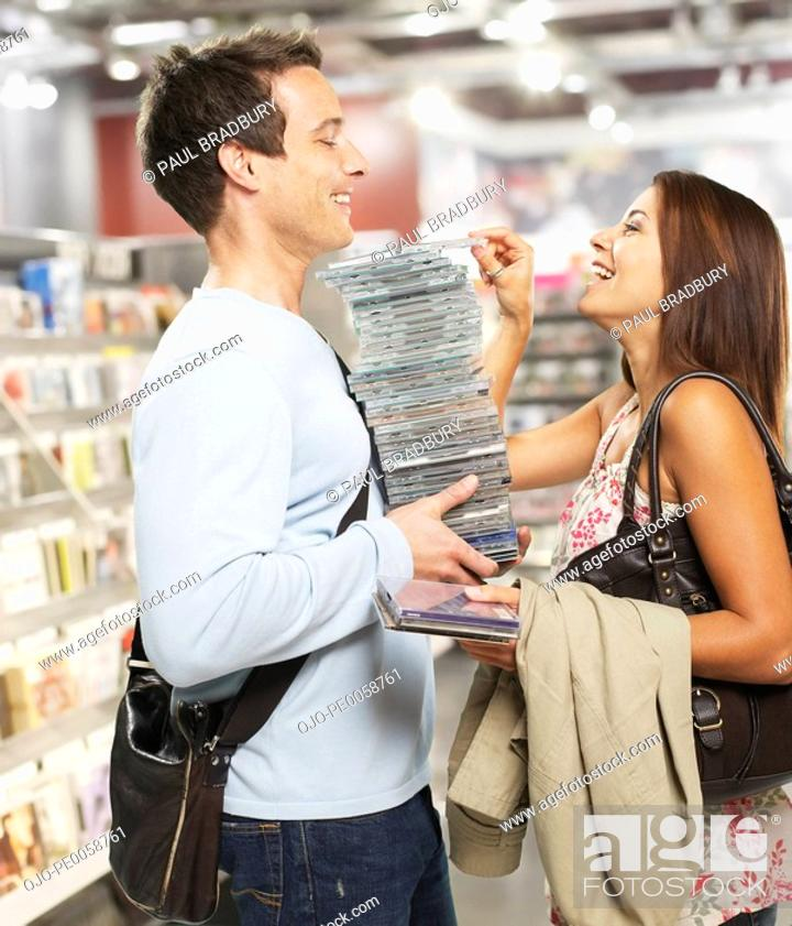 Stock Photo: Man holding stack of CDs with woman putting one more on top.