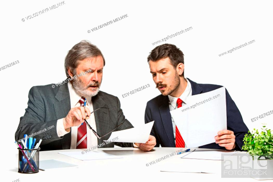 Imagen: The two colleagues working together at office on white studio background. They actively and emotionally discussing current plans.