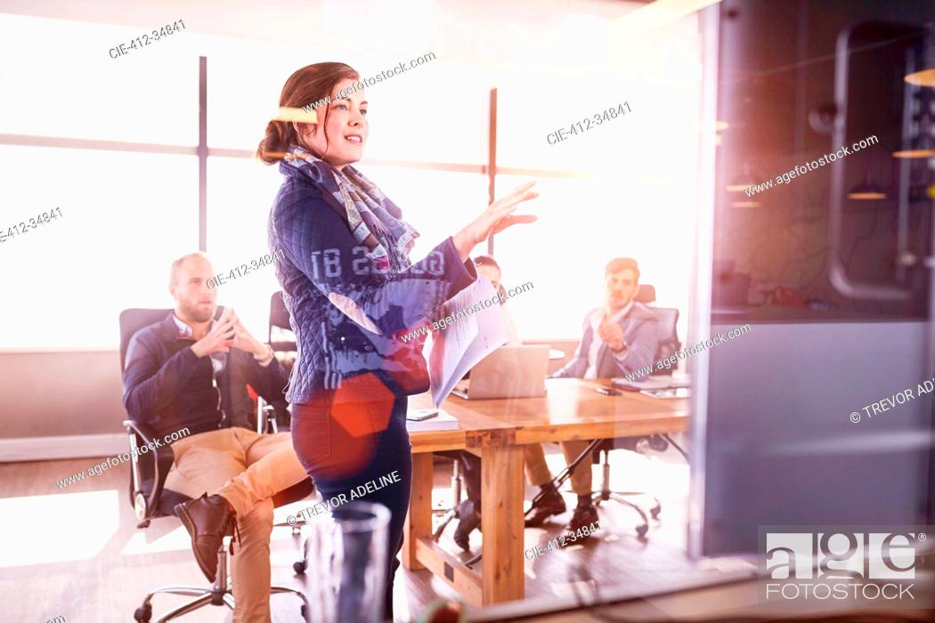Stock Photo: Businesswoman leading meeting at television screen in sunny conference room.