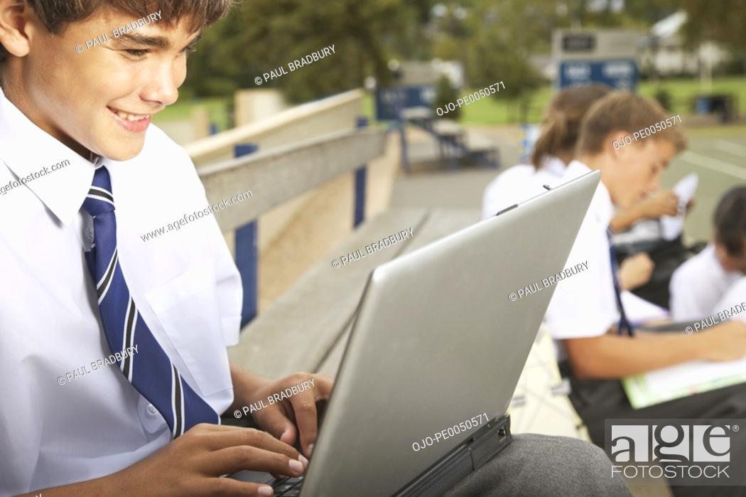 Stock Photo: A student outside using a laptop.