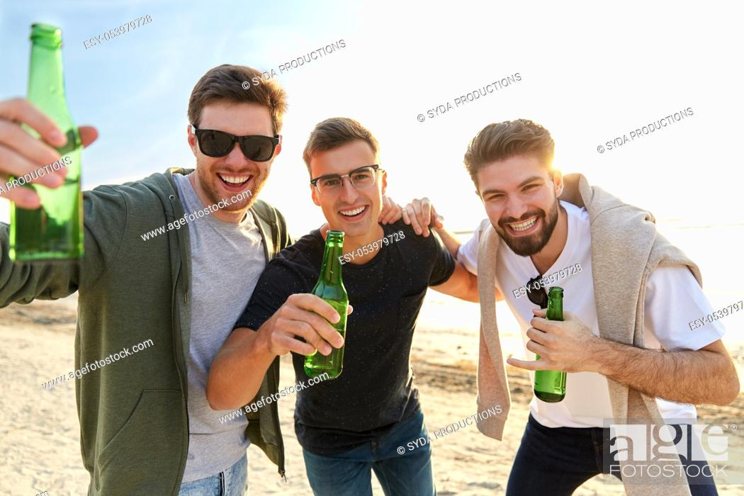 Stock Photo: young men toasting non alcoholic beer on beach.
