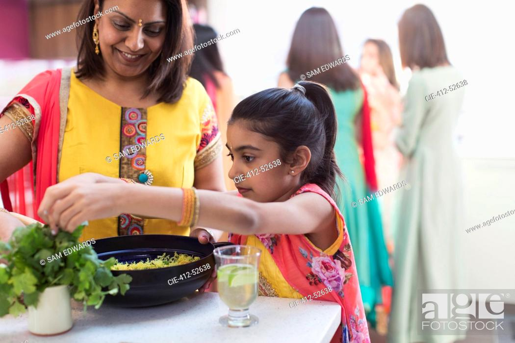 Stock Photo: Indian mother and daughter in saris cooking with fresh herb in kitchen.
