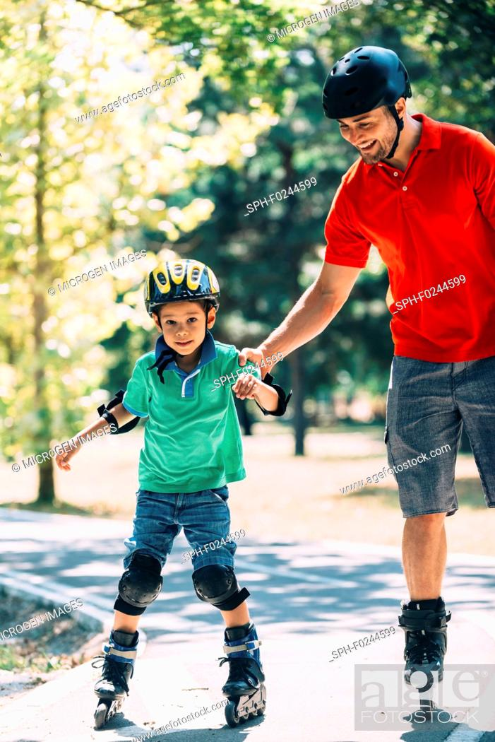 Stock Photo: Father teaching son roller skating in park.