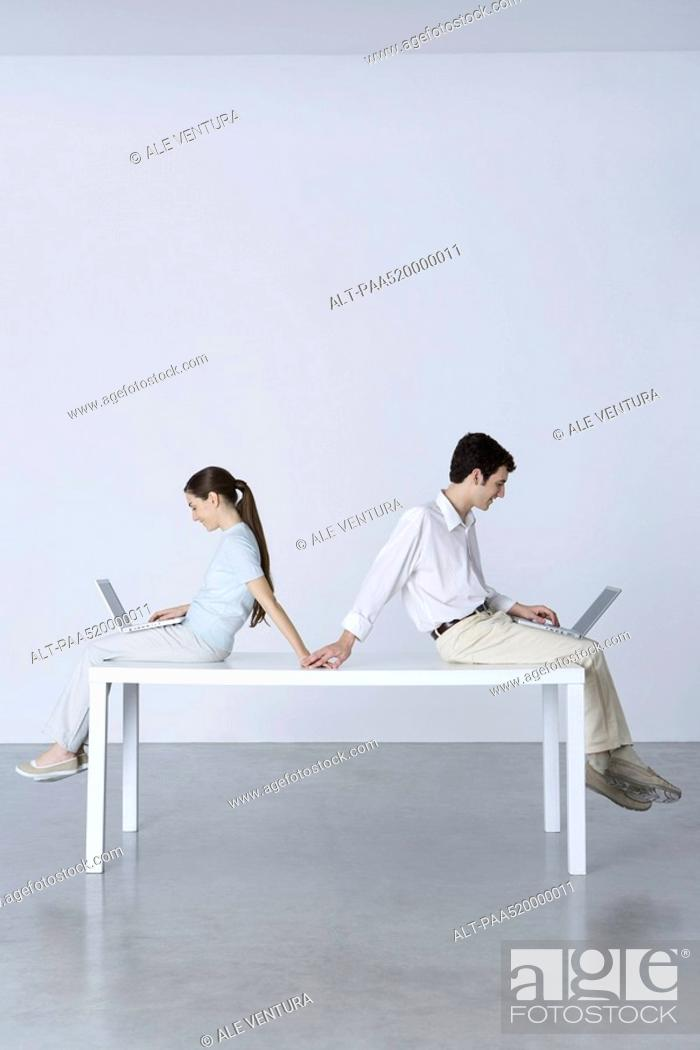 Stock Photo: Couple sitting back to back, using laptop computers, holding hands.