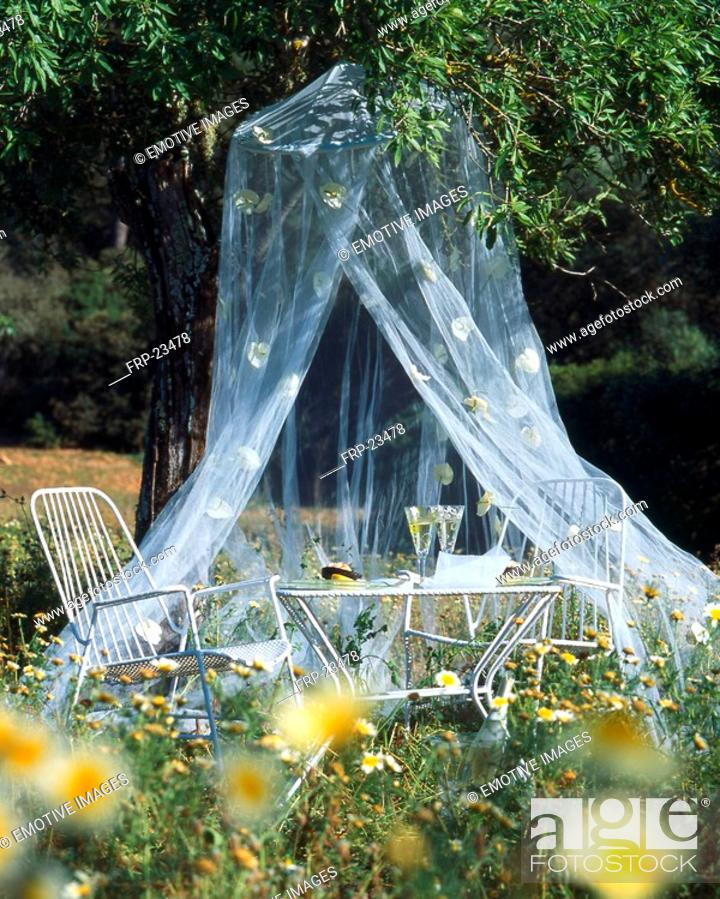 Stock Photo: Cosy seat beneath a mosquito net.