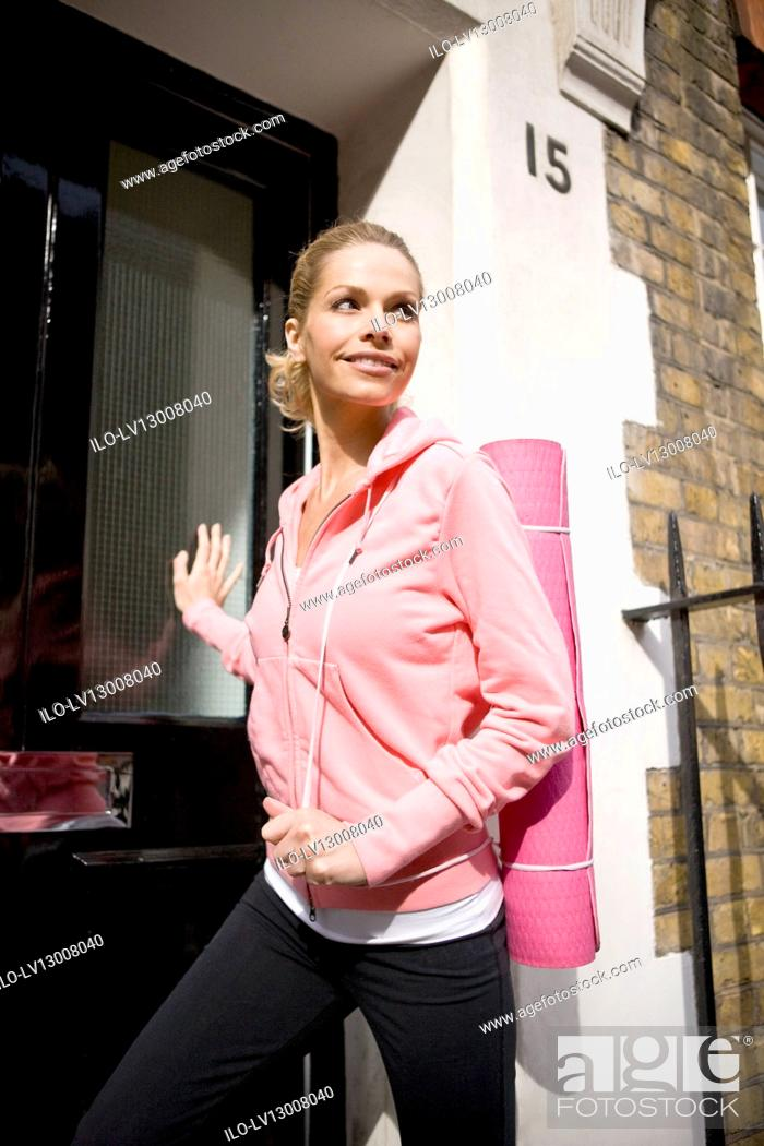 Stock Photo: A mid adult woman leaving her house, carrying a yoga mat.