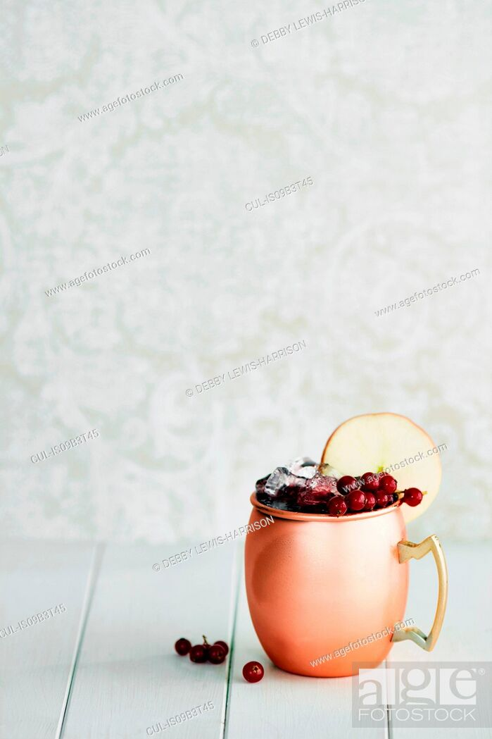 Stock Photo: Non-alcoholic cocktail in copper mug with berries and apple slice.