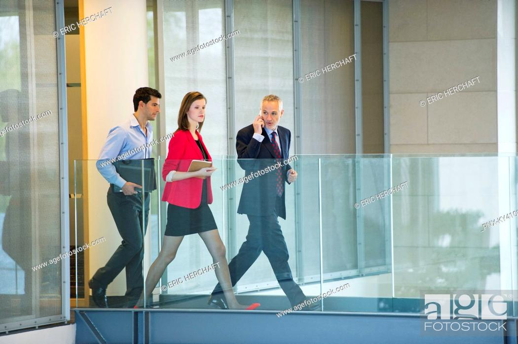 Stock Photo: Business executives walking in an office corridor.