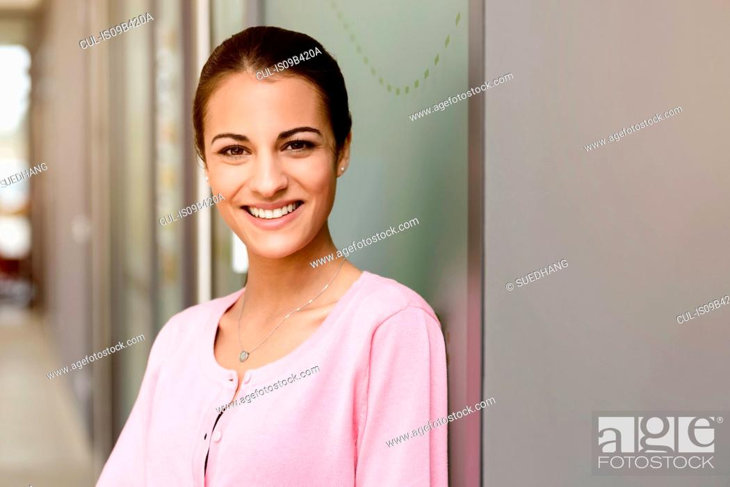 Stock Photo: Young businesswoman in pink blouse in office corridor.