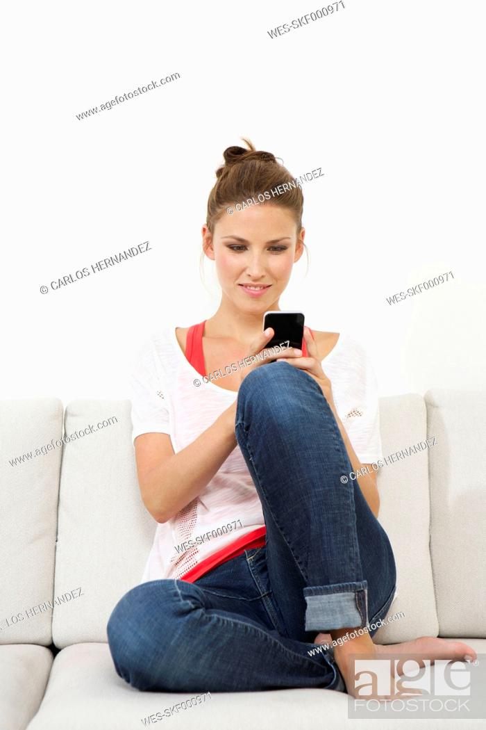 Stock Photo: Germany, Berlin, Young woman sitting on couch and using smart phone.