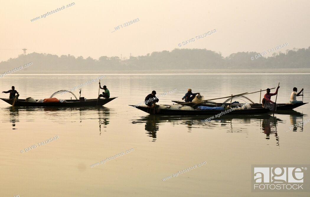 Stock Photo: Guwahati, Assam, India. January 30, 2019. Fishermen lays their fishing net at the Brahmaputra River during sunset.