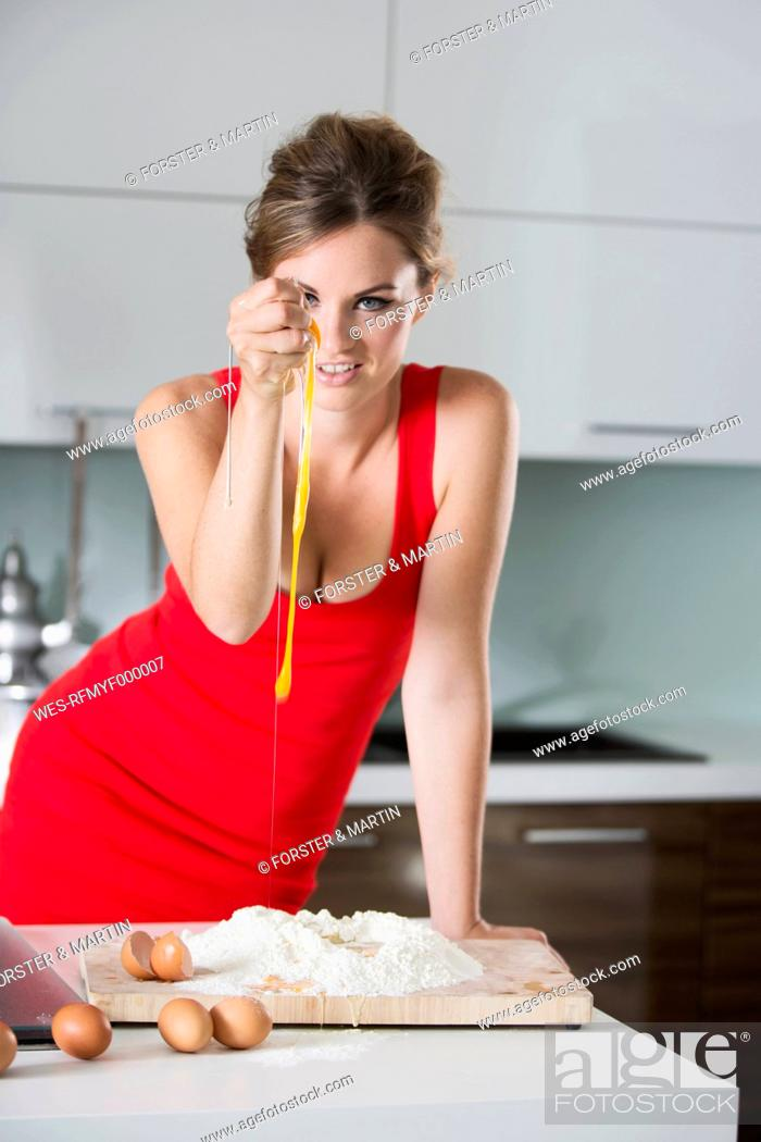 Stock Photo: Germany, Young woman squeezing eggs in flour.