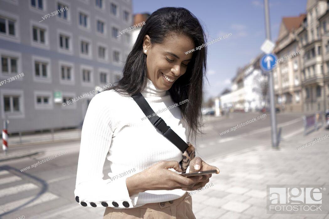 Imagen: Brazilian woman on the street, using smartphone, Munich, Germany.